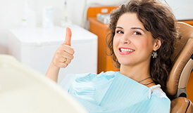 Woman with thumbs up in dental chair