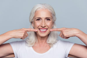 Senior woman pointing to healthy smile
