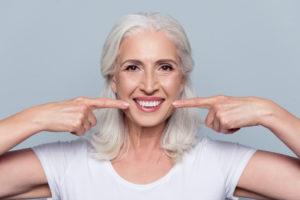 Senior woman pointing to healthy smile