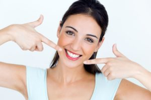 woman pointing to her white smile