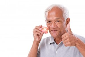 Man holding dentures gives thumbs up to denture care tips